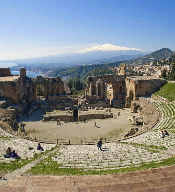 Taormina, Messina, Sicily. This staging form is an Amphitheatre. This particular Amphitheatre is a Roman Amphitheatre, this is shown by the distinctive D shaped performing area.