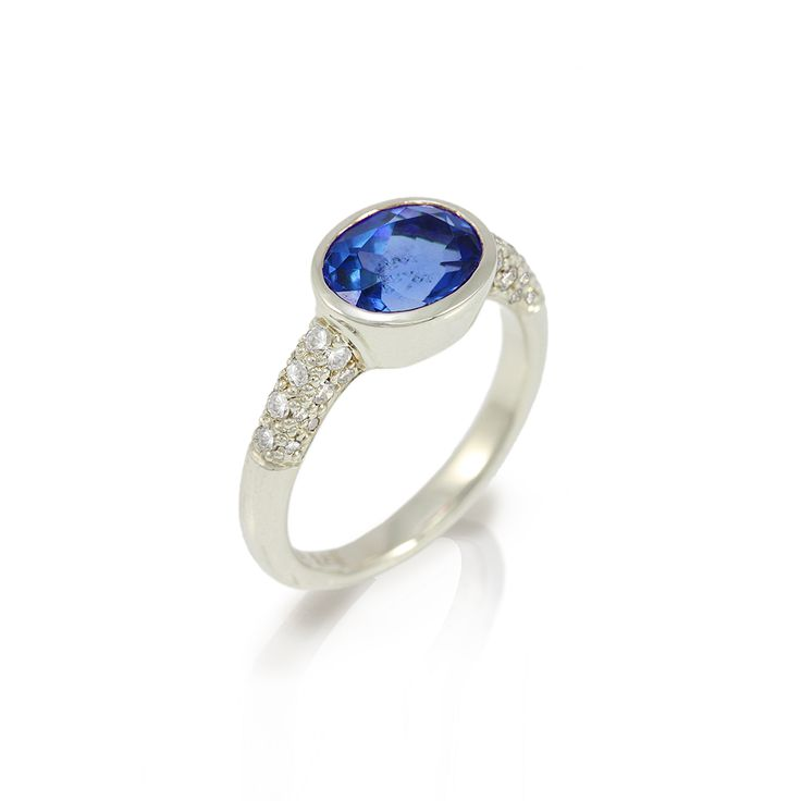 Margot sapphire ring in white gold  Hand-made in 9 carat white gold, 32 white diamonds on the shoulders (total 0,32 carats) support a large blue faceted sapphire (8×6 mm).