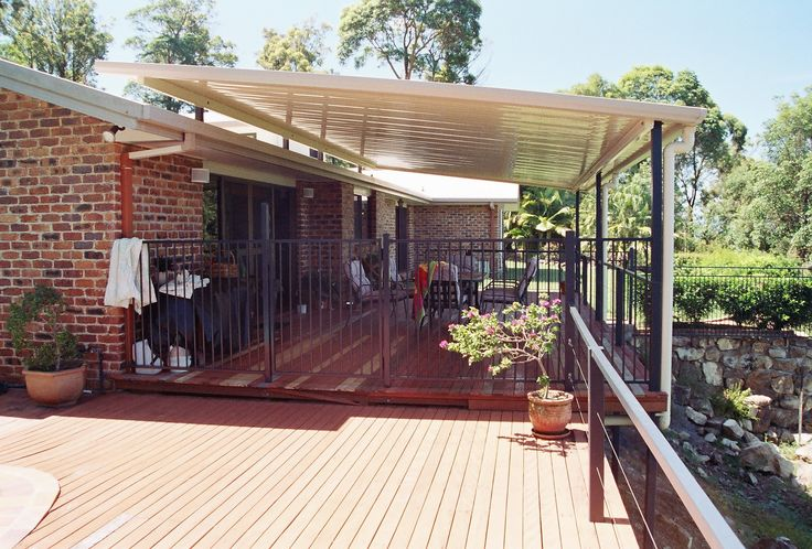 Deck built around a pool with a single skin fly-over roof.