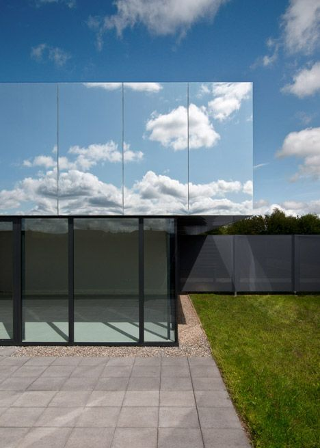 The mirrored roof of this children's care centre reflects the surrounding treetops and skies.