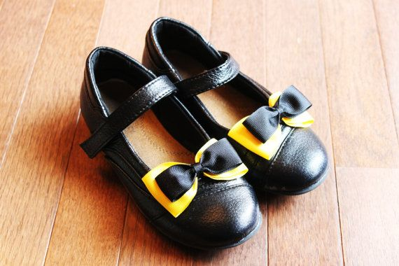 This is a Pair of Yellow and Black Bow on Girls Bow Shoe Clips. Pictured on youth size 1 shoes.