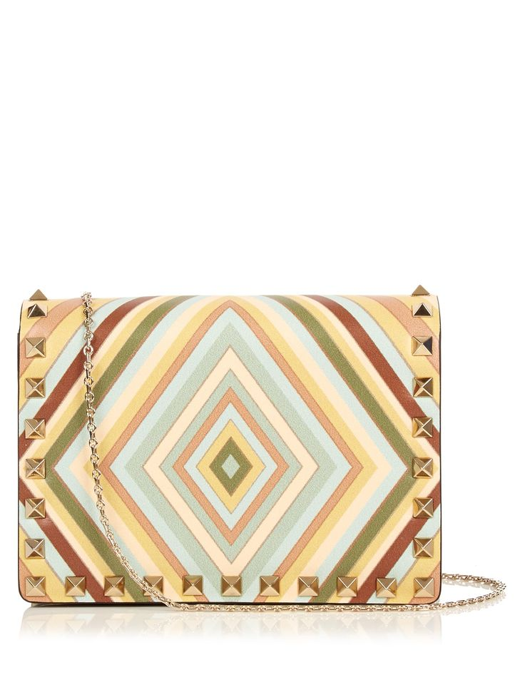 Valentino tackles the season's nostalgic vibes with total authenticity, plucking this pastel-hued 1975 print straight from the archives. It's showcased to beautiful effect on this leather cross-body bag, which is neatly detailed with a trim of pale gold-tone metal Rockstuds – a seamless blend of old and new. Let the powdery hues complement a sky-blue skirt at summer events.