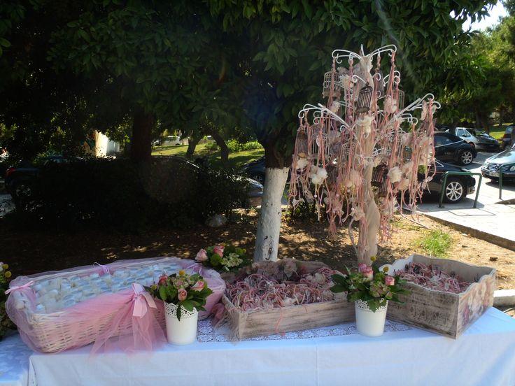 Κρεμαστές αέρινες μπομπονιέρες σε λευκές και ροζ αποχρώσεις, διακοσμούν με χάρη των τραπέζι των μπομπονιέρων και και συνθέτουν μια vintage εικόνα που θα αγαπήσετε. Γλυκά διακοσμούν το τραπέζι.
