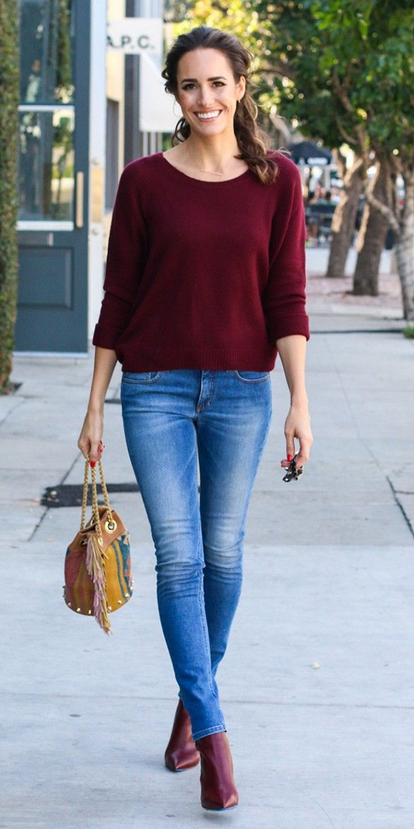 Louise Roe dressed up a casual burgundy blouse and jeans with a colorful textile bucket bag and pointy burgundy ankle boots