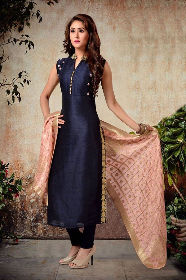 Get chic with this enticing navy blue designer suit featuring a pitta embroidered chinese collar followed by a pin tucked torso featuring gold fabric buttons for décor while peach resham flower motifs accentuate the side panels of torso in a beguiling charm; flare falls plain with the side borders done in zari, pitta & kundan work in an exemplary finish! This suit is accompanied by matching leggings & contrasting peach dupatta but design of dupatta may slightly vary from the website