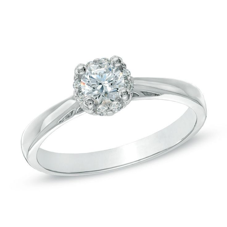Classic and elegant, this dazzling diamond engagement ring is certain to win her heart. Beautifully crafted in 14K white gold, this sweet style features a 1/4 ct. certified Canadian diamond center stone, boasting a color rank of I and clarity of I1. A halo frame of smaller round accent diamonds wraps this center stone in a sparkling embrace. A lovely design, this ring captivates with 1/3 ct. t.w. of diamonds and a bright buffed finish. Certified Canadian diamonds are accompanied wit...