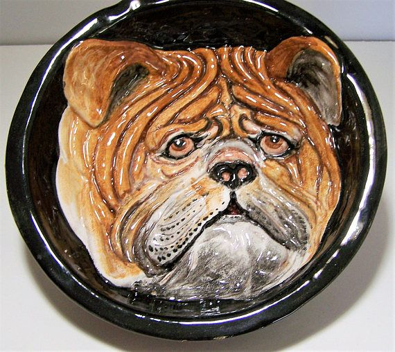 Vintage Majolica hand painted English Bull dog wall plaque or bowl Black background, with a relief bulldog face, very detailed and well done Signed on back Made in Italy 9 1/2 inched diameter upper edge, 7 inches diameter lower edge, 2 1/4 inches high Traditional red ware under the glaze, there is one 5x8mm chip on the edge exposing the red clay, there is also a place next to it where someone covered up a chip with a black sharpie, and a place where the black glaze was lightly appli...