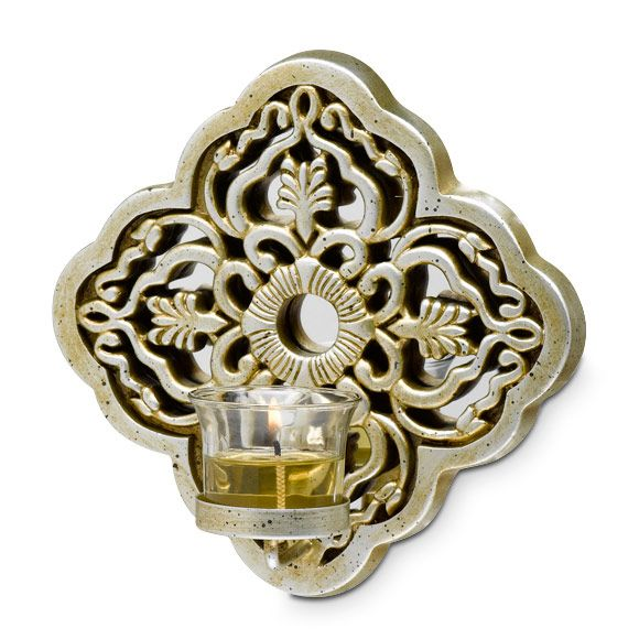 """INSPIRATIONAL VOTIVE SCONCE Item #:  P91160 Ornate cross-inspired design shimmers with a metallic glow when lit by candlelight. Display the sconce in a pair for an even greater impact. Glass votive cup for use with votives and tealights sold separately. Resin with metal dish. 8""""h, 3½""""d. Reguilar price: $45.00 each  SALE! $20.00 each"""