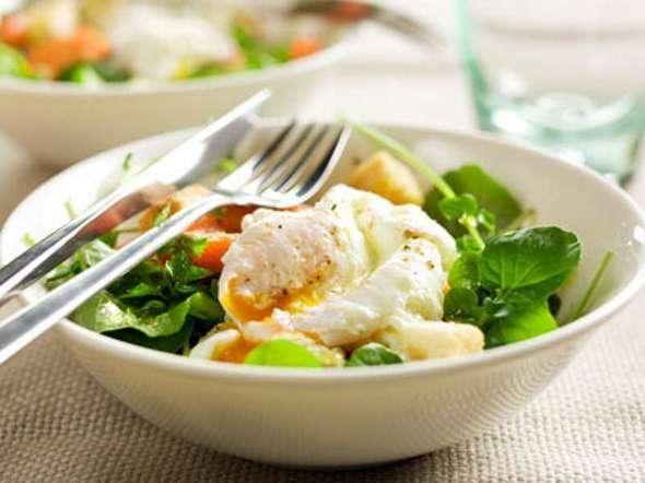 Salada de agriões e cenoura com ovos escalfados, cubos de pão torrados e ervas frescas
