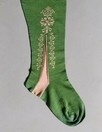 A knitted green silk lady's stocking, early 18th century, with contrasting pink floral clocks and ankle panels This stocking was probably worn with the previous lot