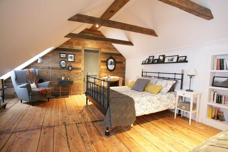 On visite une chambre mansardée dans une maison canadienne ancestrale, rénovée avec le cachet du bois et des lambris.
