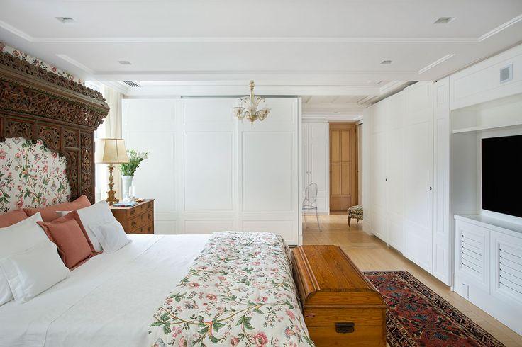 Decoração de apartamento com cara de casa. No quarto de casal tons neutros, cabeceira de madeira, roupa de cama floral, cômoda de madeira, baú de madeira e flores.