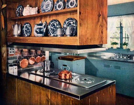 """This 20-year-old """"period kitchen"""" in New Canaan, Connecticut, was proof for House Beautiful in 1950 that """"old and new materials can be happily married. Beautiful old boards, old weather-beaten brick live harmoniously with new wallpaper and fresh blue enamel paint, stainless steel, and rubber tile. These last two are as durable and carefree as modern engineers and technicians know how to make them."""""""