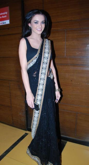Bollywood actress Amy Jackson in beautiful black designer #drape #saree with #embroidered border work paired with #designer sleeveless #saree blouse from #designer Sabyasachi.