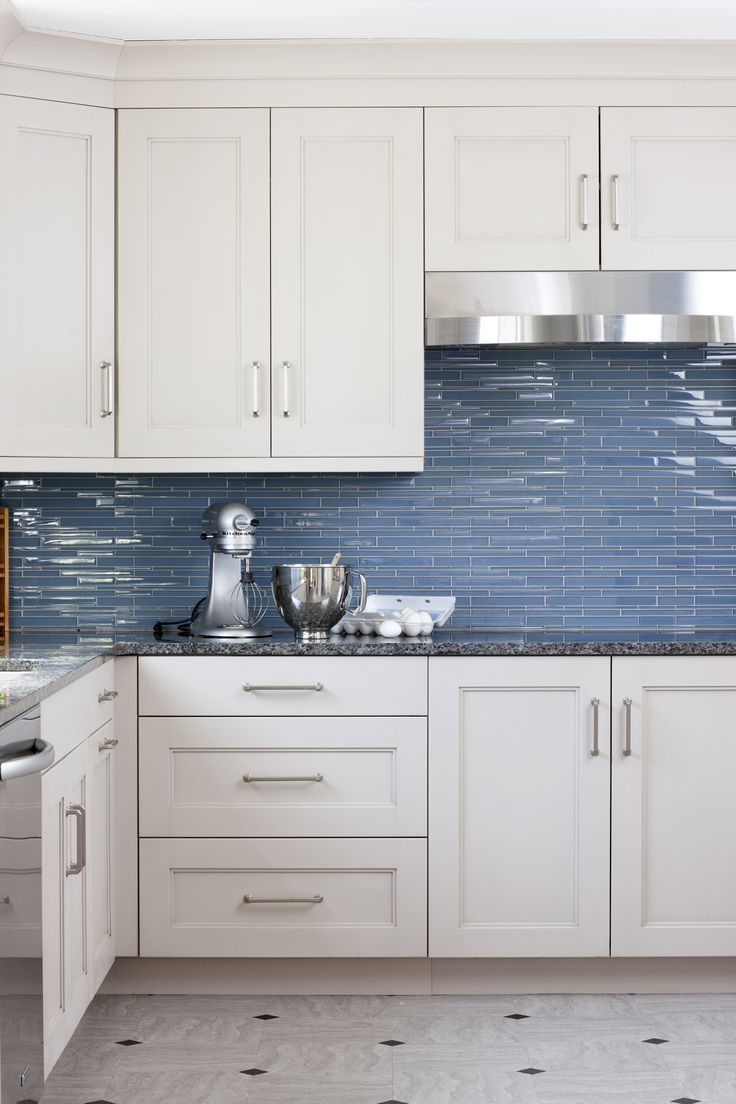 White and blue kitchen features white cabinets adorned with satin nickel  pulls paired with black countertops and a linear blue glass tiled backsplash .