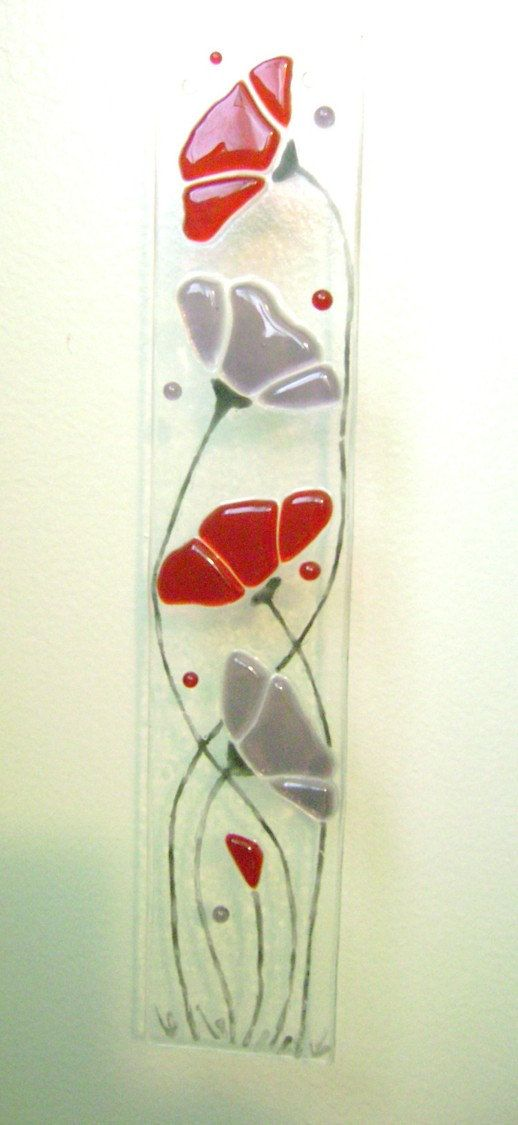 I cut red transparent glass for the Poppies and purple for the other flowers. The stems were painted with glass enamel paint. I then fused everything together in my kiln for a day to 1300 degrees. This Suncatcher is 10 x 2 and has two holes drilled into the top to hang in a window.