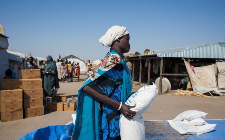 A mother carries a bag of cereals for her family while boxes of USAID-donated oil are waiting to be distributed to refugees living in Alagaya Camp. WFP provides each refugee with a daily ration of 475 grams of cereals, 60 grams of pulses, 30 grams of oil and 10 grams of salt. (11 May 2015, Photo: WFP/Ala Khier)