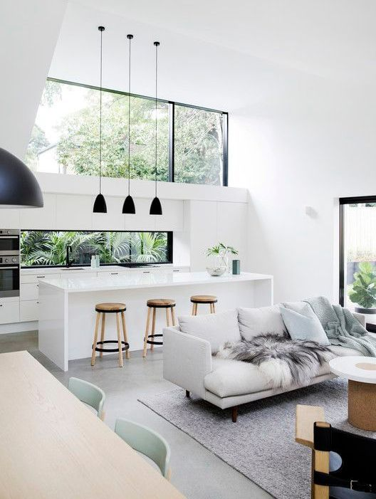 Clean open space: White kitchen and living room with black decor.