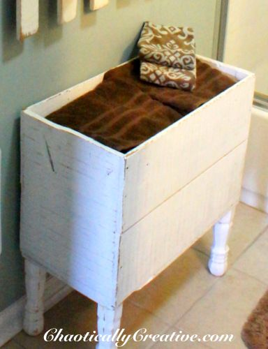 Adding table legs to an old box makes  great towel storage.