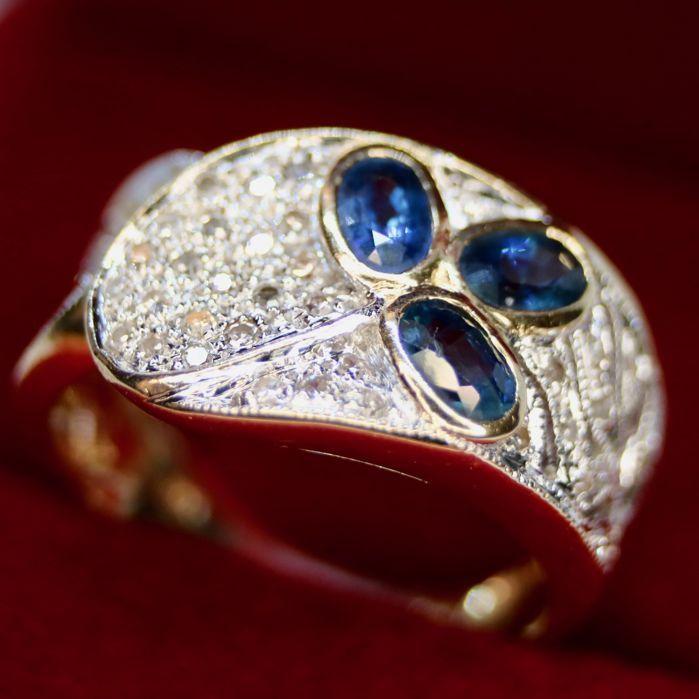 14kt. Handkrafted mooie brede ring met mooie blauwe saffieren en diamanten H/SI in zeer goede staat.  14 kt geel / wit goud brede ring met 3 natuurlijke ovaal knippen blauwe saffieren van ca. 060 ct en ongeveer 35 oude geslepen diamanten van ca. 1 mm mooi design. Goldsmith vakmanschap.Goud 585 hallmarkedDiamanten:Kleur: Wesselton / witDuidelijkheid: SISaffieren: ovale facet knippen geen krassenKleur: blauw' Edelstenen zijn vaak behandeld om kleur en helderheid te verhogen. Dit is niet…