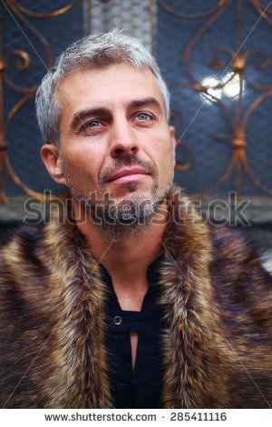 Portrait of a sexy man in wolf fur and ornamental medieval window on background.