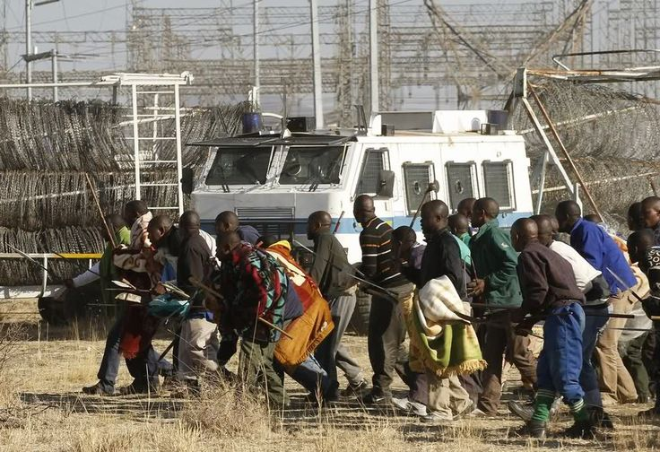 Marikana: A year on | Protesting miners approach the police.