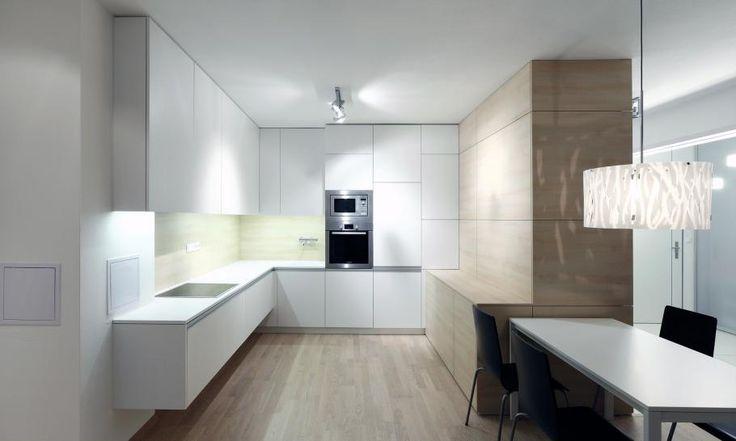 Kuchyňu do tvaru U sme navrhli z dvoch štandardných laminátových dekorov. Na prvý pohľad obyčajné materiály k sebe dobre pasujú a robia kuchyňu čistou a útulnou. Pracovnú časť kuchyne sme odľahčili zavesením na stenu. Skriňová zostava s dreveným dekorom oddeľuje kuchyňu od vstupnej časti a funguje ako šatník.