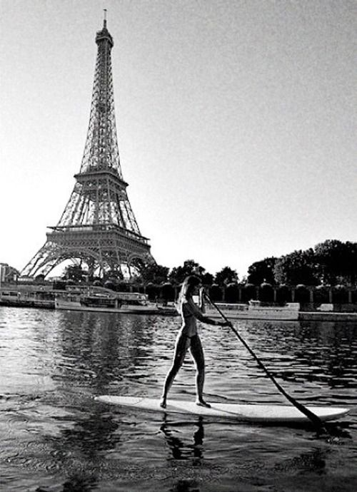 stand up paddle surfing next to the eiffel tower, how cool!