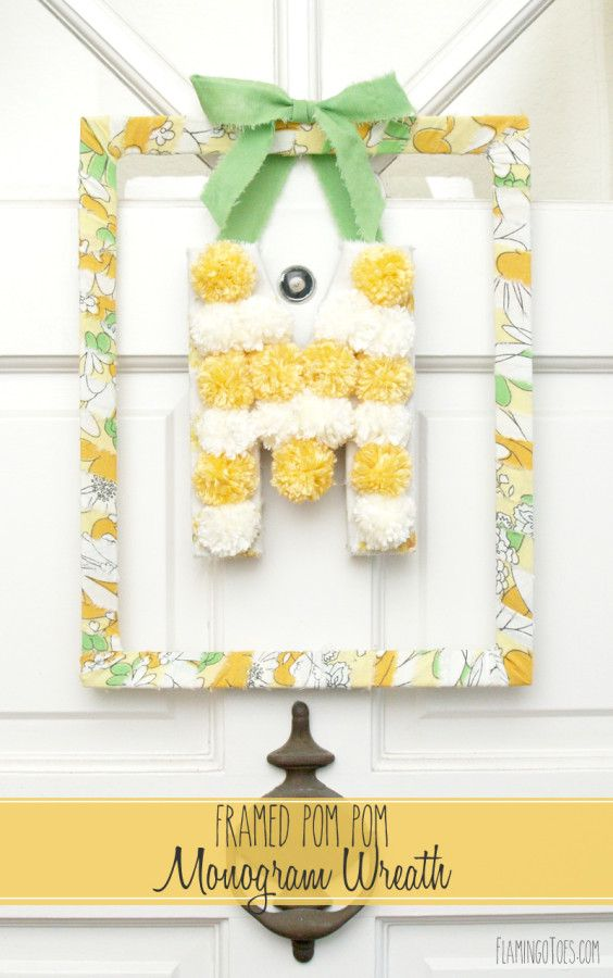 Framed Pom Pom Monogram Wreath -- love the vintage-look fabric wrapping the frame.  This could be a cute idea for a bedroom wall or the door of a girl's room.