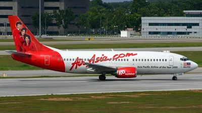 AirAsia (MY) Boeing 737-3T0 9M-AAR aircraft, with ''3 Stewardess photo on the tail''  the sticker ''Asia Pacific Airline of the Year 2003'' in black letters on theairframe, skating at Malaysia Kuala Lumpur International Airport. 31/12/2005.