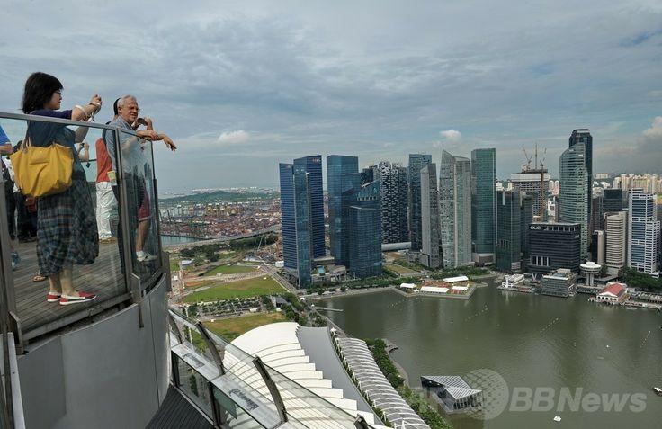 シンガポールの高級リゾートホテルのマリーナ・ベイ・サンズ(Marina Bay Sands)の屋上にある展望台から景色を眺める人々(2014年5月20日撮影)。(c)AFP/ROSLAN RAHMAN ▼23May2014AFP 高級ホテルの屋上プールで景色を満喫、シンガポール http://www.afpbb.com/articles/-/3015704 #Singapore #Marina_Bay_Sands #Observation_deck