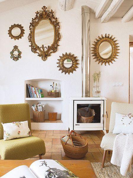 Salón rústico decorado con espejos vintage y chimenea exenta