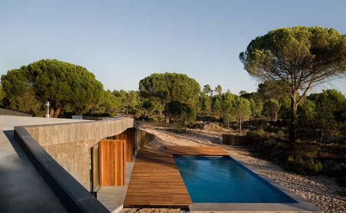 Casa Monte na Comporta in Grândola, Portugal is a house that sits in its surroundings as if it had always been there yet it also manages to look completely fresh, cool, new and spectacular.     The house's undulating shape echoes the gently sloping sand dunes, and its hard and angular surface planes contrast beautifully with the rounded shapes of the surrounding trees.