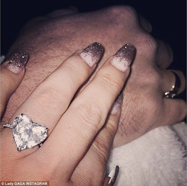 Loved up: Lady Gaga posted a picture of herself holding hands with fiancé Taylor Kinney while showing off her heart-shaped diamond engagement ring in an Instagram picture posted on Sunday evening