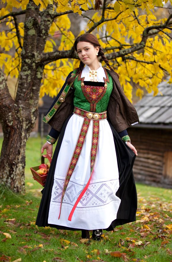 Hardanger bunad with a green silk and a black woolen skirt. The white apron has inlaid embroidery, which is known as Hardanger embroidery.