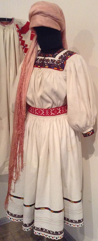 Married woman's attire from Transcarpathian region of Ukraine. It consists of a shirt, a skirt, a belt, and a kerchief. The embroidery patterns are colorful, but there aren't many