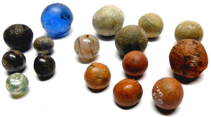 """Małe kulki ze szkła, kamienia i gliny, znalezione w Gnieźnie. Służyły w późnym średniowieczu i okresie nowożytnym jako """"kamienie"""" do ulubionych przez dzieci gier i zabaw. Wszystkie te kulki znaleziono w pobliżu różnych gnieźnieńskich kościołów. Prawdopodobnie zostały zagubione przez uczniów szkół przykościelnych."""