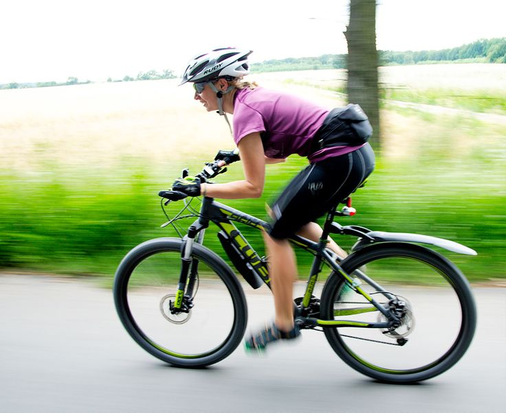 A woman cycling a mountain bike fast along a road in the country side. Her body position is bent low with her elbows bent.