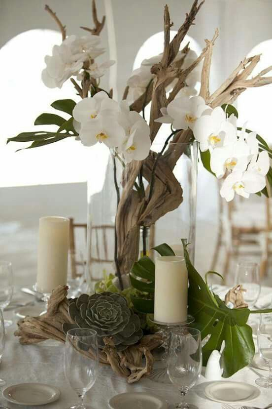 Tall centerpiece of driftwood and orchids with succulents and tropical leaves