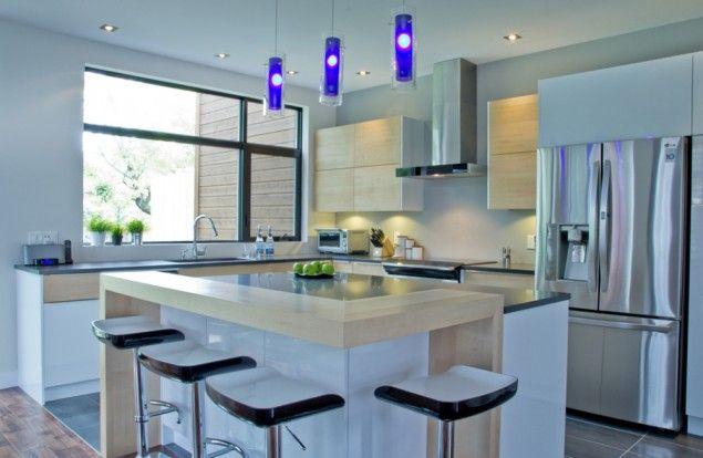 L'îlot et les armoires de la cuisine ont été réalisés en thermoplastique lustré et en placage d'érable naturel. Le tout est harmonisé avec un comptoir en quartz (aile de corbeau) et un comptoir-lunch en placage d'érable.