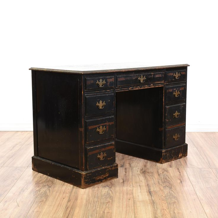 This shabby chic desk is featured in a solid wood with a distressed black paint finish. This kneehole desk has 8 drawers in varying sizes, shiny brass hardware and simple carved trim. Perfect for a small home office! #americantraditional #desks #kneeholedesk #sandiegovintage #vintagefurniture