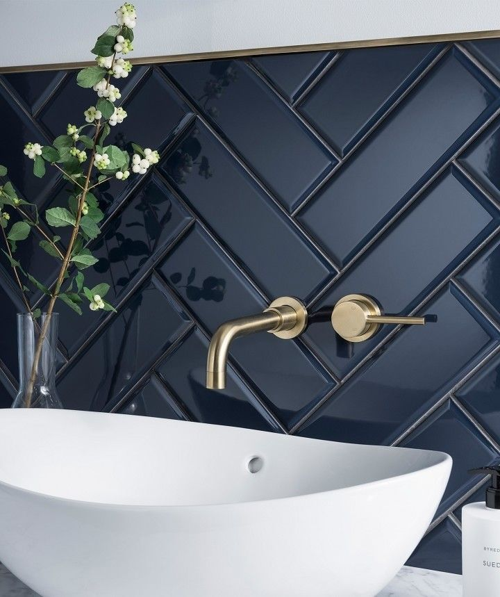Dark herringbone bathroom tile with brass fittings and white sink. Modern bathroom with beautiful contrasts in colors and textures.