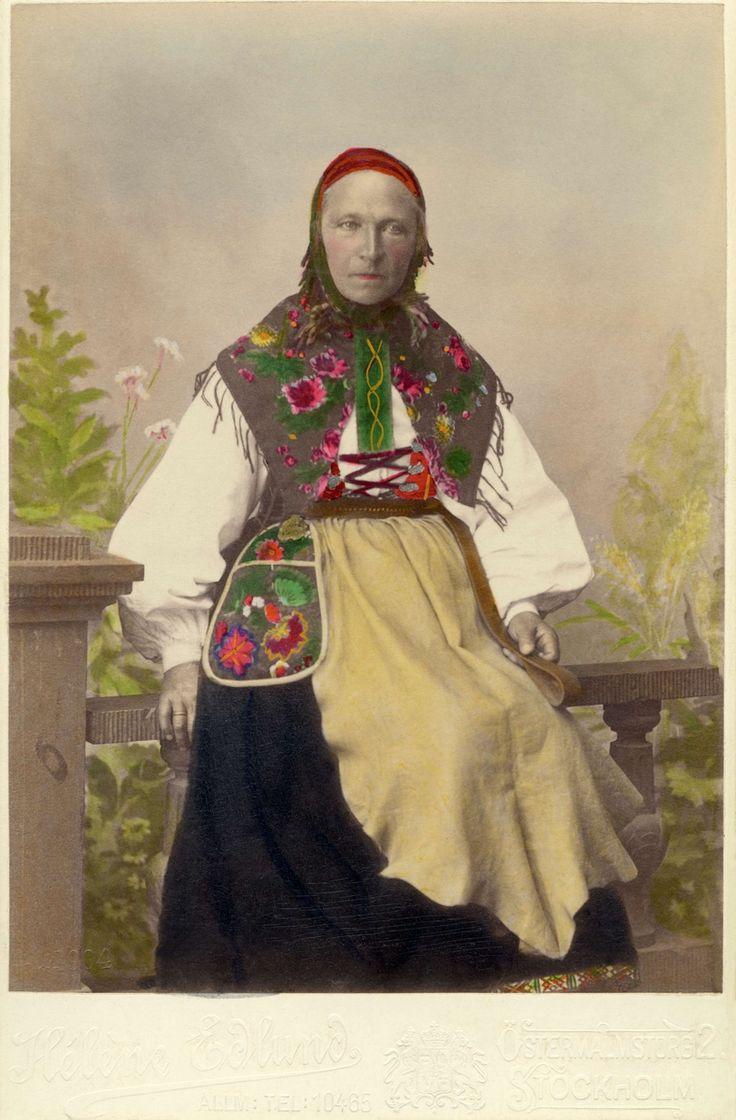 """""""Floda utställningen 1897."""" En kvinna poserar i en folkdräkt med skinnförkläde"""