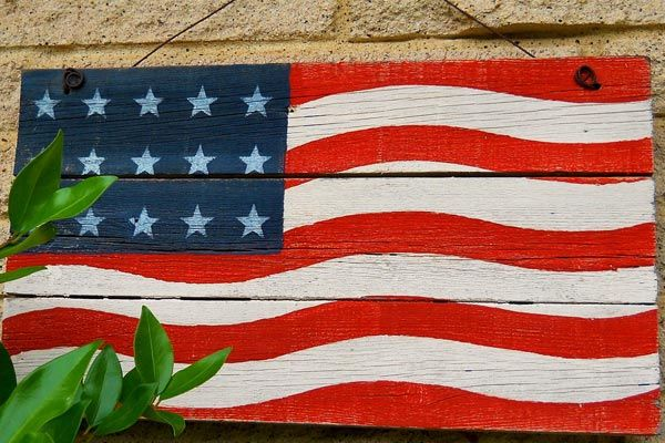 american flag painted onto wood boards and hung on an exterior wall