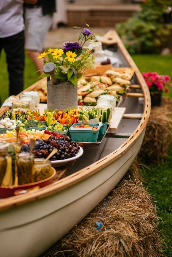 outdoor buffet in a canoe rustic wedding decor / http://www.deerpearlflowers.com/wedding-food-bar-ideas/