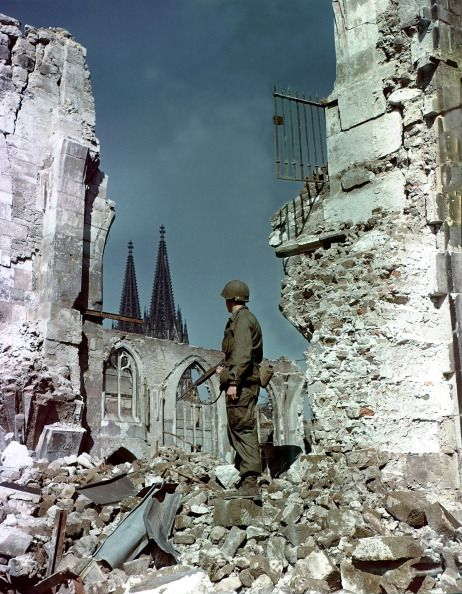U.S. Army Private Brookey is standing in the ruins in front of Cologne Cathedral, which suffered seventy hits by aerial bombs during World War II. May 1945. In June 1945 American troops used it as a rifle range. Most of the town in this area was flattened during the war. Cologne, Germany. (Photo by Galerie Bilderwelt/Getty Images)