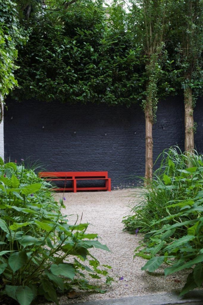 Love this wall colour, gives more depth in garden with trees in front and popping colour of red.