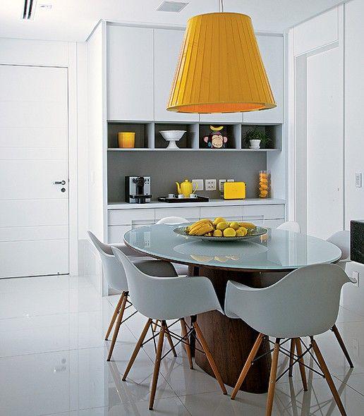 Acredite se quiser: a luminária pendente amarela é de tecido. A peça alegra a sala de almoço, onde predomina o branco. Projeto da arquiteta Ligia Resstom