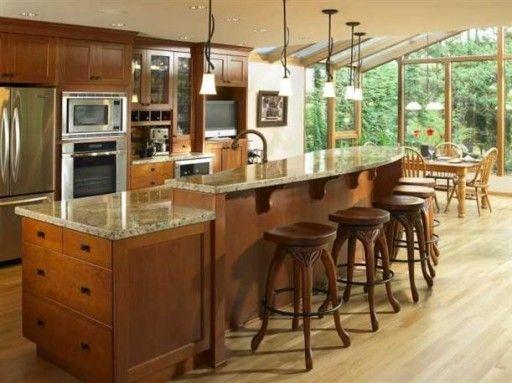 Многоуровневый кухонный остров с барной стойкой успешно справляется и с функцией зонирования кухни