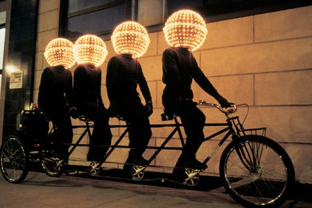 Eric Staller, BUBBLEHEADS, 1987	   	 	   The BUBBLEHEADS, a bicycle built for 4 riders, each dressed in black and wearing a sphere covered with 200 computerized lights.